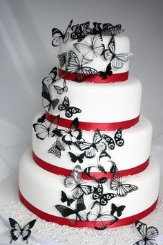 White wedding cake with black butterflies and red ribbon accents