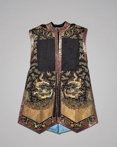 Chinese embroidered silk tunic with matching green skirt; with dragons; the sleeveless tied tunic of deep purple with gilt thread dragons above waves; the matching skirt with panels of sea green with gilt dragons alternating with phoenix, divided by borders of purple and gold
