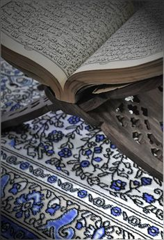Old Book of Quran Open on Wooden Stand
