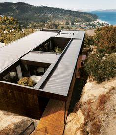 The Kingston house remains unobtrusive and well camouflaged on its hillside site despite the architects' use of modernist geometry. The o...