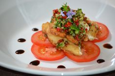 Scratched fish served on vine tomato with sweet balsamic dressing.