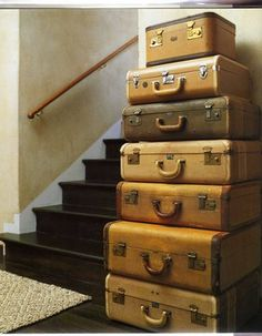 A stack of vintage suitcases standing in a hall.