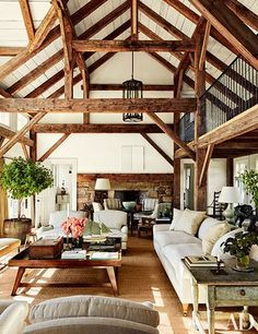 Reclaimed timber beams accent the barnlike common room at Lynn and Sir Evelyn de Rothschild's Martha's Vineyard, Massachusetts, home, which was built by Rivkin/Weisman Architects and decorated by Mark Cunningham; the landscape design is by Horiuchi Solien. Circa-1930 lanterns (one is pictured) from Ann-Morris hang from the ceiling, and an artwork by Callum Innes is mounted above the fireplace.