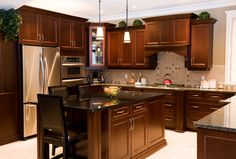 This rich, cozy kitchen features lush dark wood cabinetry and island with dining space and jet black countertop.