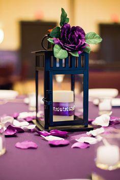 Simple purple wedding reception decor idea - purple table cloths, flower petals, metal lantern + purple flowers {Candid Moments Photography}