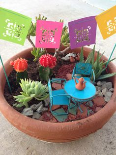Mexican fairy garden. Martha Stewart craft punch flag banner. Michael's terra cotta pots. Broken pottery for the path. Home Depot for succulents and pot. Local store for table and chairs. Painted skewers for poles.