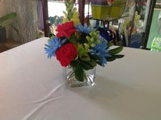 Mixed centerpiece in cubed vase of red carnations, blue dyed daisies, green athos poms, yellow snapdragon and greens