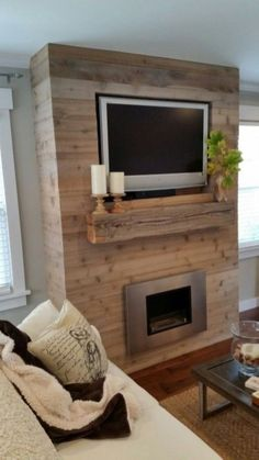 This DIY fireplace feature wall can be made on a budget, since you'll cut labor costs by constructing this one-of-a-kind piece yourself. The inexpensive statement piece uses repurposed wood to make a rustic yet modern display for this couple's home. Fireplace Feature Wall, Simple Fireplace, Home Fireplace, Faux Fireplace, Fireplace Remodel, Fireplace Surrounds, Fireplace Design, Ethanol Fireplace, Fireplace Ideas
