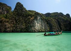 A longtail in clear waters with limestone cliffs in the background in the Phi Phi area.