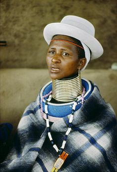 Africa | People. A woman from the Ndebele tribe in South Africa wearing traditional attire and a Western-style hat.