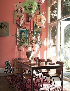 The dining room of a Dutch home features brightly hued lanterns suspended above the table.