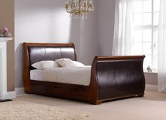 Dreams Bruges Bedstead - Our Bruges sleigh bed is constructed in hard solid wood which is complimented with soft faux leather for a high-end sophisticated looking bed.    The leather pads are styled with stitching detailed lines and bordered with intricate metal studs adding to the grandeur feel of the Bruges bedstead. The exquisite look of our Bruges bed is finished with sculpted details on the ends of the headboard and footboard.