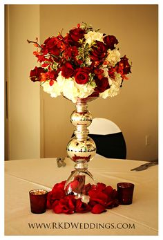 Red roses and red mokara orchids' natural beauty is enhanced next to white hydrangea. A silver vase and red rose petal complete this stunning look