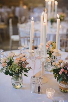 Small white candelabras with crystal details as table centre pieces - Image by Sam Gibson - Bride wears lace wedding dress at a rustic wedding in Almonry Barn Somerset. Bridesmaids & Groomsmen outfits from Debenhams