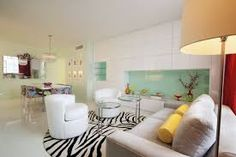 modern living room sofas rug: modern apartment living room  modern apartment living space decoration with white sofa and white wall tiles also zebra rug and green kitchen