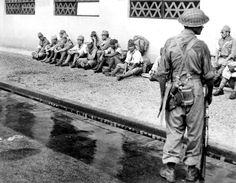 An Indian soldier of the 5th Indian Division stands guard over Japanese POWs outside the former Japanese Imperial Army headquarters in newly liberated Singapore following the Allied liberation of Singapore (Operation Tiderace), which was initiated in coordination with Operation Zipper, the liberation of Malaya. Singapore, British Straits Settlements (now, Republic of Singapore). September 1945.