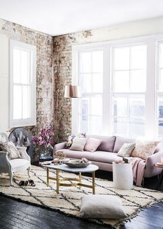 A beautiful, girly living room. Dark hardwood floors, pink sofa, exposed brick wall, area rug and a lot of natural light. Home Decor Goals