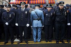 Law enforcement officers stand, with some turning their backs, as New York City Mayor Bill de Blasio speaks on a monitor outside the funeral for NYPD officer Wenjian Liu in the Brooklyn borough of New York January 4, 2015. Tens of thousands of law enforcement officers from across the country gathered on Sunday for the funeral of the second of two New York City policemen killed last month in an ambush that galvanized critics of Mayor de Blasio.