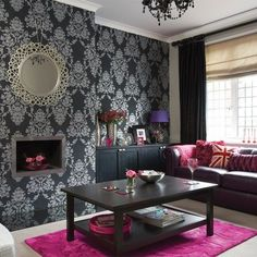 Black and silver wallpaper, pink accessories and bursts of rich plum create a show-stopping effect in this dramatic living room.