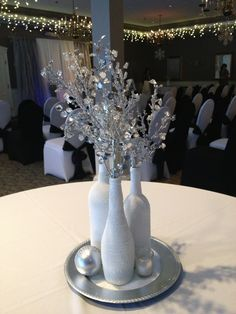 I made 12 of these centerpieces for a New Years Eve wedding. Spray painted bottles white, then a coat of spray adhesive & rolled in Epsom salts. Placed on a silver charger, more salt spread around the tray. Add a votive candle & a silver ornament. And gorgeous silver picks inside the bottles. I love them!!