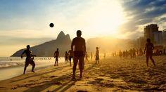 Drenge der spiller fodbold på stranden i Rio, Brasilien