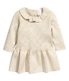 Lichtbeige gemêleerd. BABY EXCLUSIVE/CONSCIOUS. Een fijngebreide jurk van zacht biologisch katoen met een ajourdessin. De jurk heeft een volantrand langs de