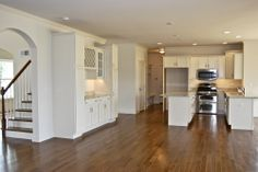 White Kitchen Shown With: Stainless Steel Appliances, Arched Entry, Lockers, Oak Hardwood Flooring and Kitchen Island.