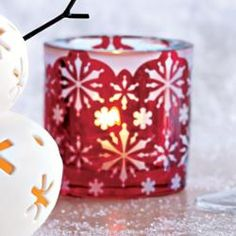 "Winter Lace Votive Holder - Icy snowflakes twinkle on a backdrop of Christmas red. Add your own tealight or votive for a festive shimmer. Crafted from glass. 3""h. Price:  $15.00 each"