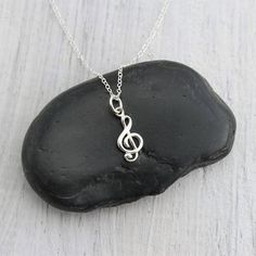 Sterling Silver Treble Clef Music Charm Necklace. The perfect silver charm for music lovers and musicians. » Sterling Silver Treble Clef Charm (18mm x 7mm) with soldered jump ring and tiny 925 genuine Sterling mark on back. » Sterling Silver Cable Chain (select from drop-down on upper