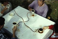 """Coffee Seeks Its Own Level. 1990. If one person alone lifts his cup, coffee overflows the other three cups. All four people need to coordinate their actions and lift simultaneously. Inspired by the principle """"water seeks its own level""""."""