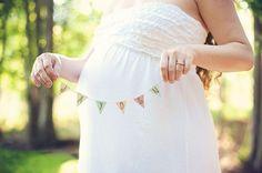 Sesión de fotos de maternidad chica sosteniendo el nombre de su bebé junto a su…