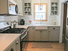 Corian Linen Counters, Benjamin Moore Senora Gray cabinets, White Dove walls, white subway tile backsplash with silver grout, farmhouse sink, industrial pull down faucet, painted Lidingo glass doors, Lantern pendant