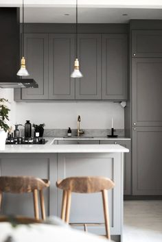 Charming dark grey kitchen with marble worktop and brass details. Although quite small and in darker color it doesn't look too crowded, mainly because one wall in the kitchen has left blank without cabinets and it makes the overall look more airy. Wooden stools behind the breakfast bar add some texture and warmth and match perfectly with Wishbone chairs around small dining table near the kitchen nook. Small kitchen area done beautifully!