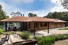 Decoração de casa de campo com madeira. Na varanda bancos de madeira, plantas, portas e janelas de madeira.