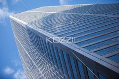 low angle shot of a tall commercial building. - Low angle view of a elegant tall office building against blue sky.