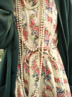 Floral dress & long layered pearls.