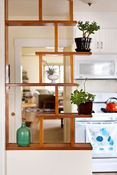 half wall with square shelves room divider- all the way across. Kid side could have activity blocks