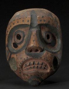 A Bella Coola mask  With pierced eyes, hollowed cheeks and grimacing mouth, in red, black and green pigments.  length 9in