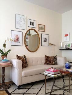 Mix it up: A big round mirror in a gold frame breaks up a gallery wall of mostly thin, modern black frames. It still looks orderly and chic, but not boring.