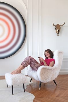 Adriana Abascal sits in a 1950s club chair with its matching ottoman, reupholstered in a Chinese lamb wool hide