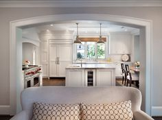 Kitchen Design. Beautiful view of the kitchen from family room.  A beautiful archway separates the family room from the crisp white kitchen.   Apron kitchen sink (bellow window) is by Rohl. #KitchenDesign #Kitchen #FamilyRoom