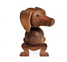"""Kay Bojesen war eigentlich ein erfolgreicher dänischer Silberschmied. Im Jahre 1951 entschloss er sich, ein Objekt aus Holz zu gestalten, welches klar und geradlinig ist, den Händen schmeichelt und das """"lächelt"""". Das """"Lächeln"""" war Bojesens Leitmotiv, das er oft erwähnte. Kay Bojesen Hund"""