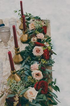 A garland centerpiece adds a wisp of whimsy and romance to practically any tablescape. This garland incorporates pastel pink roses and deep red flowers — which echo the jewel tone of the table's candles — for a holiday centerpiece that is equal parts traditional and contemporary. Via Junebug Weddings
