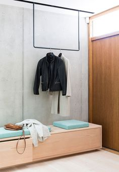 Entryway with clothing rack in steel and a wooden bench. The clothing rack has LED lights in the rear that glows the concrete wall up.