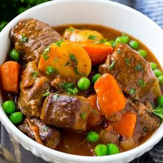 A bowl of slow cooker beef stew with meat, carrots, potatoes and peas.