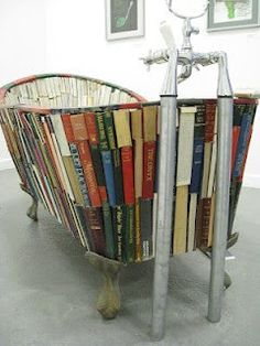HOW IS THIS EVEN POSSIBLE< I MUST KNOW!!!  LOL    A new way of reading in the tub  Bath tub made out of book bindings