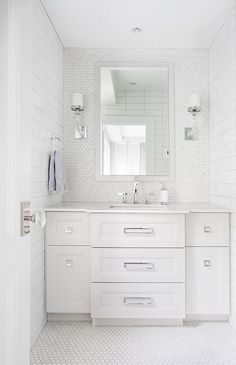 White and gray bathroom features Crystal Cube Single Sconces positioned flanking a light gray framed vanity mirror mounted on white marble hex backsplash tiles over a light gray washstand fixed on white marble hex floor tiles between shiplap walls and accented with square ring pulls and a white quartz countertop fitted with a sink paired with a polished nickel faucet.