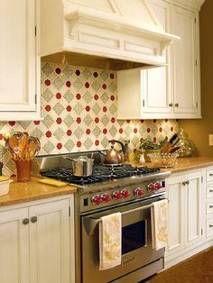 love this kitchen with antique cream-colored cabinetry, quartz stone countertops, sage, cream and red tiled backsplash...