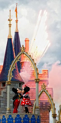 Mickey and Minnie sharing a kiss at the top of the castle <3