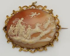 A Victorian oval shell cameo brooch  Carved to depict the ascent of Helios to the skies in his chariot, accompanied by the Muses and preceded by Eos, collet set within an open scrollwork mount, with engraved decoration and applied bead detail, width 7.5cm.